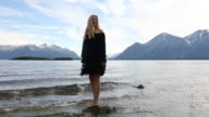 Female model hops off rock at lake edge, walks forwards