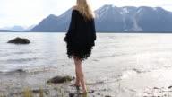 Female model hops onto rock at lake edge, looks off
