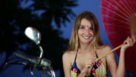 MS Female model in bikini with facial jewelry on motorcycle twirling parasol / Montezuma, Punteranes, Costa Rica