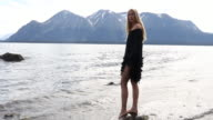 Female model pauses on rock at lake edge, dabbles toes