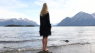 Female model pauses on rock at lake edge, looks off
