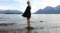 Female model pivots on rock at lake edge, dress catches breeze
