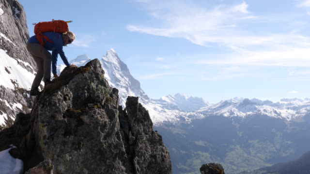 Female mountaineer ascends rock pinnacle above mountains,valley
