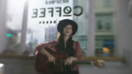 SLO MO. Female musician poses with acoustic guitar in downtown coffee shop venue.