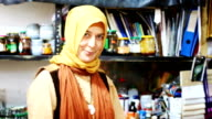 Female Muslim leather worker presenting finished shoe