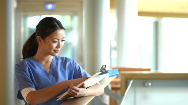 kvinnlig sjuksköterska kontrollera anteckningar i en sjukhuskorridor
