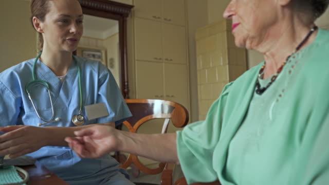 Vrouwelijke verpleegkundige bezoeken van de oude vrouw en haar bloeddruk thuis meten.