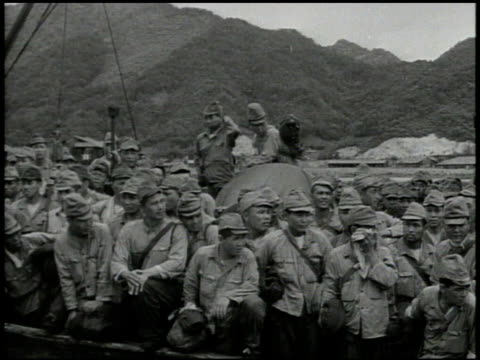 Female nurses standing on dock welcoming back Communist soldiers soldiers getting off boat walking pass billboard w/ mother holding baby family Japan...