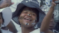 Female Orlando Pirates fan smiling and dancing, Johannesburg Available in HD.