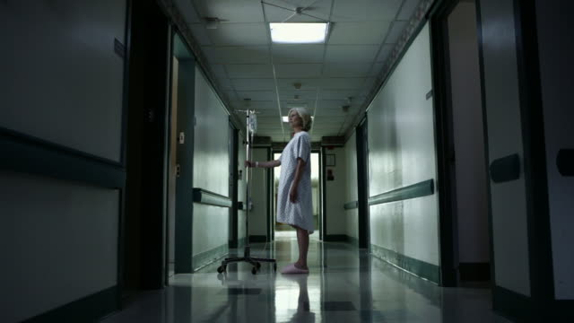 Female patient with intravenous drip in hospital corridor