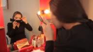 Female performer putting fake eyelashes on