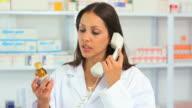 Female pharmacist calling while holding a bottle of drug