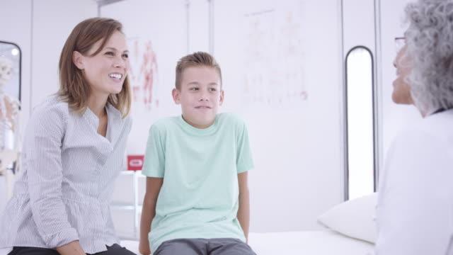 4K UHD: kvinnliga läkare chatta med en ung pojke och hans mamma på examen rummet