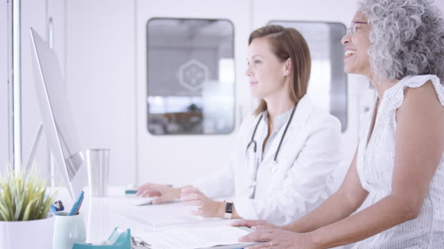 4K UHD: Female physician sitting at a computer with her patient