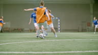Female player scoring goal during friendly indoor soccer match