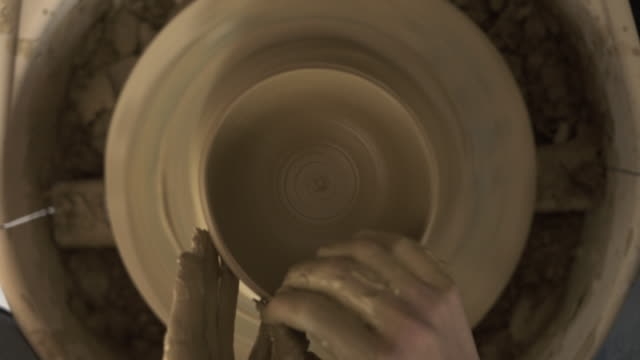 female potter shaping pot from lump of clay on potters wheel  / Kyoto, Japan