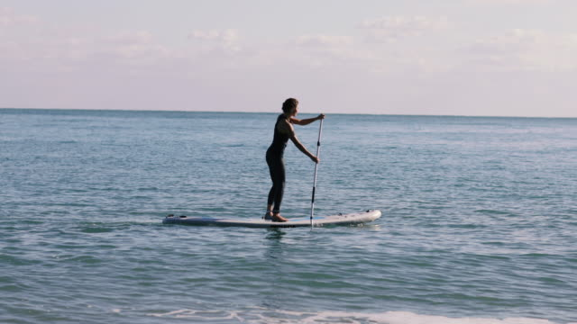 Female practice paddle boarding in the sea