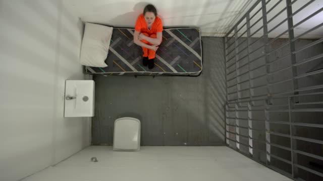 4K AERIAL: Female Prisoner in Jail Cell Sat on bed