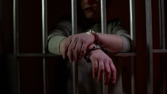 4K DOLLY: Female Prisoner in Jail Cell with Handcuffs