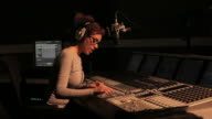 Female Radio DJ working in recording studio