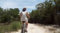 Female rides bike through beach path