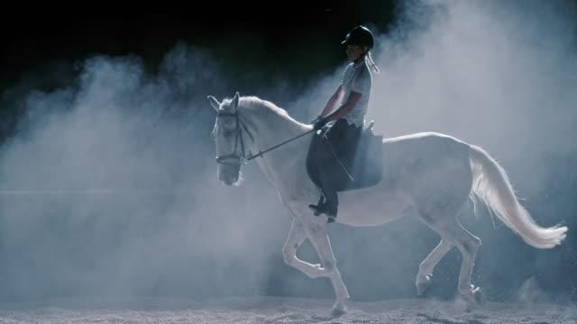 SLO MO LD Female riding a white horse at night