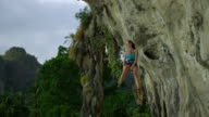 WS Female rock climber being lowered down by rope and smiling / Krabi, Thailand