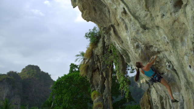 MS Female rock climber reaching to clipping rope into karabiner on rock face/ Krabi, Thailand