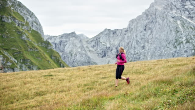 DS Female runner descending a mountain down a grassy meadow on a sunny day