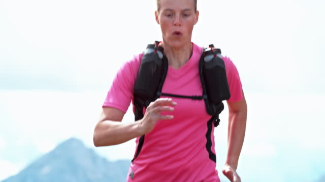 SLO MO Female runner running across a mountain meadow in sunshine