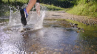 SLO MO Female runner running across a small creek