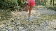 SLO MO TS Female runner running across dried up stream