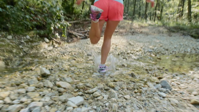 SLO MO TS Female runner running across dried up stream