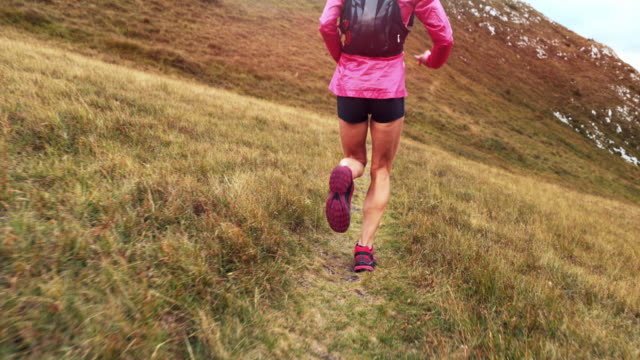 SLO MO Female runner running on a high mountain meadow