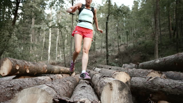 SLO MO DS Female runner running over a stock of logs in the forest