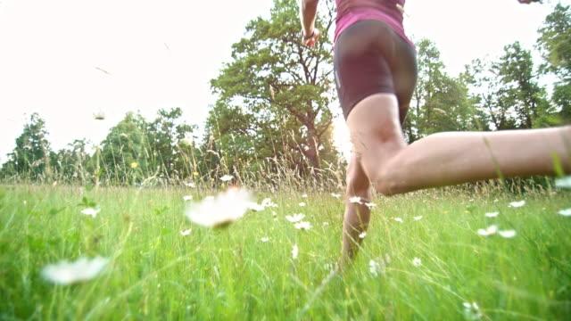 SLO MO Female runner running through high grass