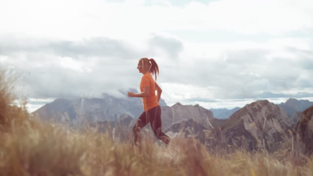 SLO MO DS Female runner running up a mountain meadow with a beautiful view