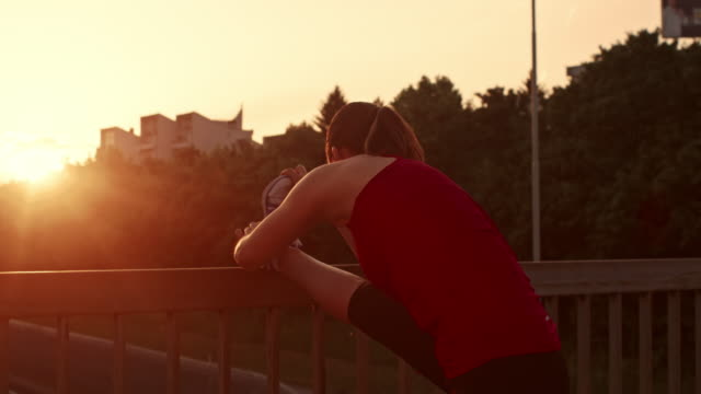 SLO MO Female runner stretching her leg at sunset