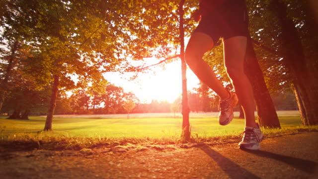 SLO MO TS Female runner's legs at sunset