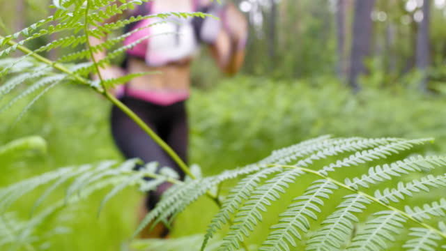 LD Female running a trail marathon crossing a forest clearing