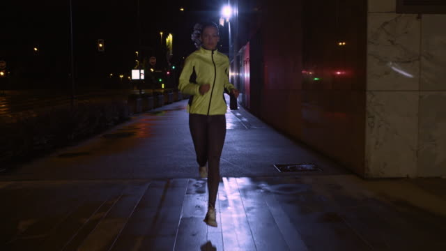 SLO MO TS Female running along a rainy street at night
