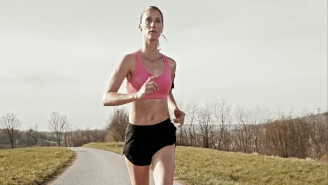 SLO MO TS donna corre su una strada con il sole