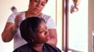 MS Female salon owner straightening clients hair in salon
