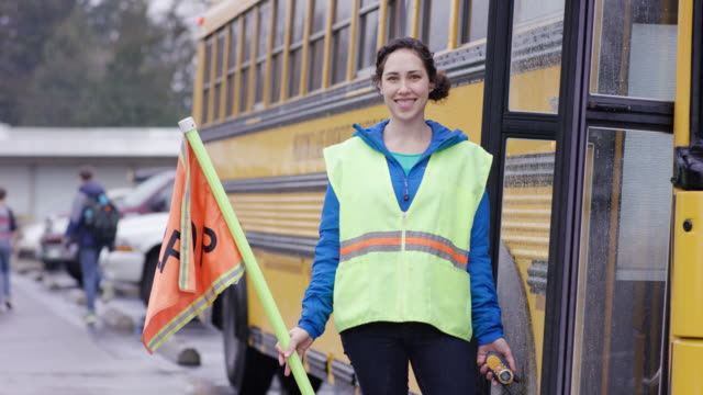 Female school bus attendant standing with stop sign by school bus