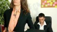 Female secretary standing in front of her boss's desk