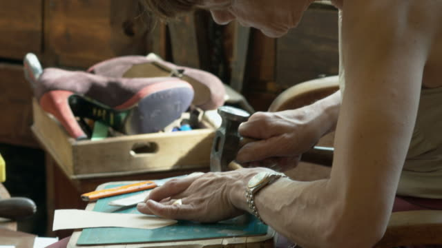 Female Shoemaker hammering Leather
