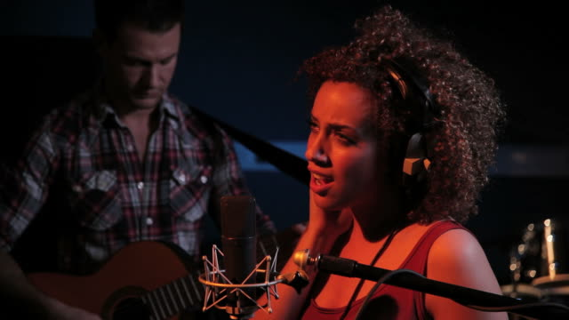 Female singing and male playing guitar in recording studio