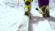SLO MO Female skier stepping into the binding and starting