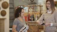 Female small business owner processing payment for female customer