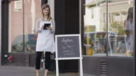 Female small business owner standing outside of her hair salon